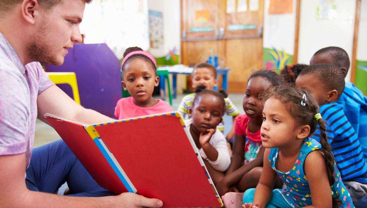 Volunteer teacher reading to a class of preschool children