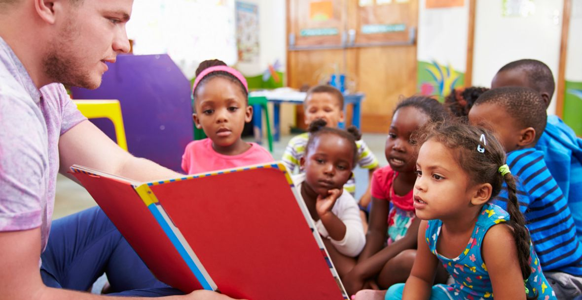 Volunteer teacher reading to a class of preschool children