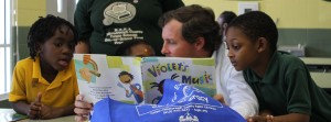 adult reading a picture book to children